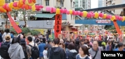 """Festive red strip of paper dangling in a Chinese new year market says: """"democracy and freedoms."""""""