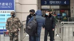 2020年1月23日安保人员在武汉市汉口火车站入口处检查人员。