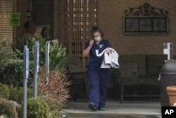 A worker at the Life Care Center in Kirkland, Wash., near Seattle, wears a mask as she leaves the building, March 2, 2020.