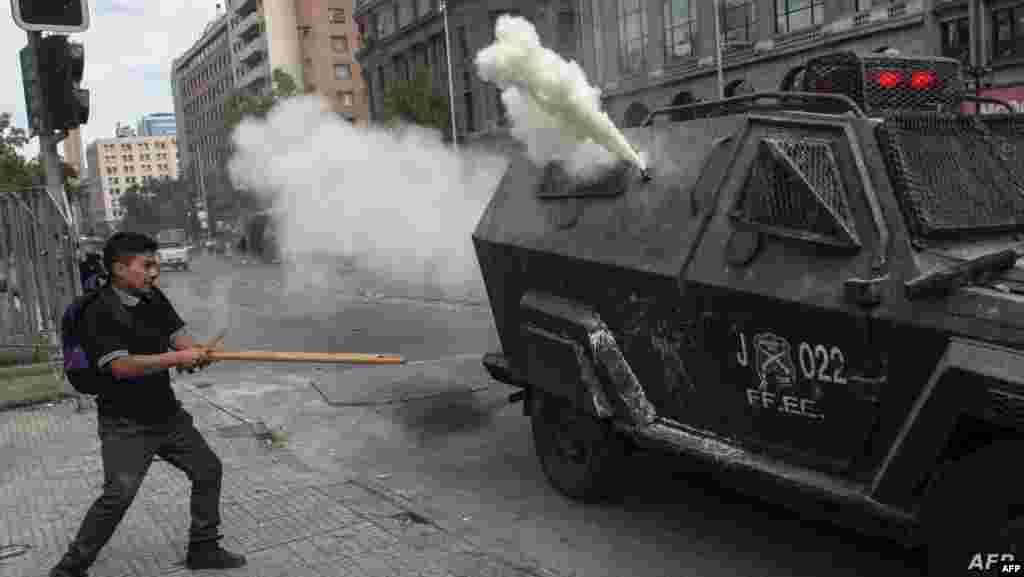 칠레에서 경제 모델과 구조적 불평등에 항의하는 전국적 시위가 열린 가운데 학생이 경찰과 대치하고 있다.