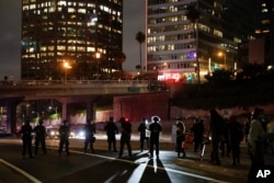 Protesters confront police officers while blocking the 110 Freeway during a protest over the death of George Floyd on May 29, 2020, in Los Angeles.