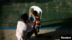 Un migrante venezolano alimenta a su hijo dentro de un coliseo donde se ha instalado un campamento temporal, luego de huir de operaciones militares en su país, según la agencia colombiana de migración, en Arauquita, Colombia el 27 de marzo de 2021.