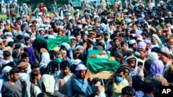 Afghans carry the body of civilians killed during fighting between the Taliban and Security forces, during their funeral in Badakhshan province, northern Afghanistan, July 4, 2021.