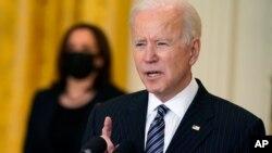 El presidente Joe Biden, en primer plano, se dirige a la nación desde la Casa Blanca, ante la atenta mirada de la vicepresidenta Kamala Harris, al fondo y con mascarilla, el 18 de marzo de 2021.