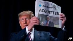 "Presiden AS Donald Trump menunjukkan surat kabar yang memuat kepala berita besar berbunyi ""ACQUITTED"" atau dibebaskan, dalama acara tahunan Sarapan Doa Nasional di Washington Hilton, hari Kamis (6/2)."