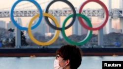 Un japonés usa una mascarilla protectora en plena pandemia frente a unos enormes anillos olímpicos en Tokio. [Foto de archivo]