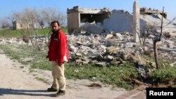 شام کے صوبے ادلب کے ایک قصبے میں سرکاری فورسز کے فضائی حملے کے بعد ایک شخص اپنے تباہ شدہ مکان کے پاس کھڑا ہے۔ فائل فوٹو
