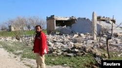 FILE - A man stands next to collapsed buildings after what activists said was an airstrike from forces loyal to Syria's president Bashar Al-Assad in Habeet, northern Idlib province, Dec. 26, 2014.