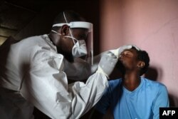 A staff member of the Ministry of Health take samples from a man during the first day of mass testing of the COVID-19 coronavirus in Djibouti on May 2, 2020.