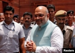 FILE - Indian Home Minister Amit Shah greets reporters upon his arrival at the home ministry in New Delhi, June 1, 2019.