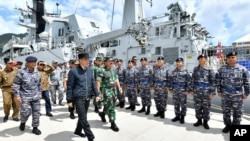 FILE - Indonesian President Joko Widodo, center, inspect troops during his visit at Indonesian Navy ship KRI Usman Harun at Selat Lampa Port, Natuna Islands, Indonesia, Wednesday, Jan. 8, 2020.