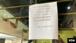Un cartel en un local de Caracas informa a los clientes que no cuentan con billetes de baja denominación para dar el cambio, Venezuela. Foto: Adriana Nuñez Rabascall - VOA.