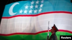 FILE - A soldier stands in front of the national flag of Uzbekistan, in Tashkent, Aug. 31, 2012.