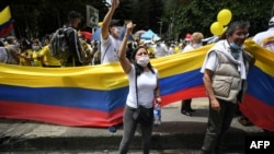 People wave the Colombian national flag during a demonstration in opposition to road blockades and violence, after a month of national protests, in Bogota, on May 30, 2021.