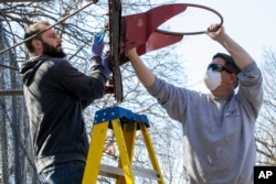 New York City Department of Parks and Recreation employees remove the basketball hoop from a court in Tompkins Square Park, March 26, 2020, in New York as part of the social distancing effort.