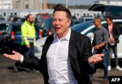 (FILES) In this file photo taken on September 03, 2020, Tesla CEO Elon Musk arrives to visit the construction site of the future US electric car giant Tesla in Gruenheide near Berlin. - Musk says he has tested positive for the novel coronavirus…