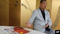 Taipan media Hong Kong Jimmy Lai menunjukkan koran Apple Daily, di Hong Kong, 1 Juli 2020.
