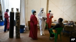 FILE - A COVID-19 patient, right, is seen to by health workers at Queen Elizabeth Central Hospital in Blantyre, Malawi, Jan. 30, 2021.