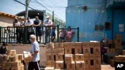 Residentes ayudan a descargar y apilar cajas de alimentos básicos proporcionados por un programa de asistencia alimentaria del gobierno en disputa conocido como CLAP, en Petare. Caracas, Venezuela. 30 de abril de 2020.