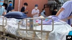北京一家發熱診所,躺在病床上的病人被推過等待檢測的居民隊伍。(20020年6月15日)