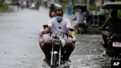 Residents on a motorcycle negotiate a flooded road due to Typhoon Molave in Pampanga province, northern Philippines, Monday, Oct. 26, 2020. A fast-moving typhoon forced thousands of villagers to flee to safety in provinces south of the Philippine…