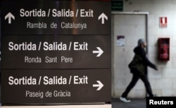 FILE - A man walks past a sign written in Catalan, Spanish and English at a train station in Barcelona.