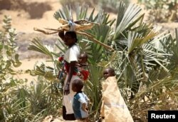 FILE - An internally displaced Sudanese woman carries her child and firewood as she walks alongside her other children within the Kalma camp for internally displaced persons (IDPs) in Darfur, April 25, 2019.