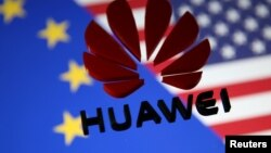 FILE — A 3D printed Huawei logo is placed on glass above a display of EU and US flags in this illustration taken Jan. 29, 2019.