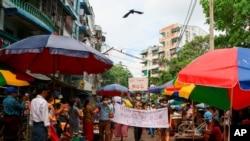 """Demonstran anti kudeta membawa spanduk yang bertuliskan """"Kami Mendukung NUG"""" yang merujuk pada kesatuan pemerintahan nasional dalam sebuah demonstrasi di Yangon, Myanmar, pada 17 April 2021. (Foto: Associated Press)"""