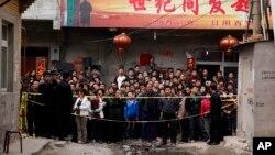 Para warga berkerumun di lokasi kebakaran di distrik Daxing di Beijing, China, 25 April 2011. Pada saat itu, setidaknya 17 orang yang diidentifikasi sebagai pekerja migran, tewas dalam kebakaran yang terjadi subuh. Kejadian yang sama di selatan pinggiran Beijing, 18 November 2017, membunuh 19 orang dan melukai 18 lainnya.