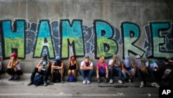 "Anti-government demonstrators sit under a bridge that has graffiti written in Spanish that reads ""Hunger,"" during a protest in Caracas, Venezuela, Saturday, July 1, 2017. Demonstrators are taking the the streets after three months of continued protests that has left dozens dead and seen the country's chief prosecutor Luisa Ortega barred from leaving the country and her bank accounts frozen, by the Supreme Court following her mounting criticisms of President Nicolas Maduro. (AP Photo/Ariana Cubillos)"