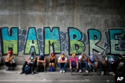 Manifestantes opositores del gobierno de Venezuela descansan bajo un puente rayado con graffitti durante una protesta en Caracas. Foto de archivo, 2017.