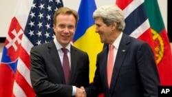 El secretario de Estado, John Kerry, saluda a su colega noruego, Borge Brende, durante la reunión de cancilleres de la OTAN en Bruselas.