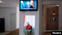 A man in a wheelchair is reflected in a mirror, as he watches a news broadcast showing Russia's President Vladimir Putin speaking at a news conference during his visit to Turkey, at a gerontological center in Stavropol, southern Russia, Dec. 2, 2014.