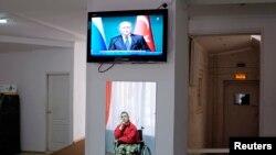 در یک مرکز درمانی در استاوروپول در جنوب روسیه، انعکاس شمايل مردی در صندلی چرخدار در آینه، زير تلويزيونی که خبر سخنرانی ولادیمیر پوتین، رئیس جمهوری روسیه، را در يک کنفرانس خبری در ترکیه نشان میدهد – ۱۱ آذرماه ۱۳۹۳ (۲ دسامبر ۲۰۱۴)