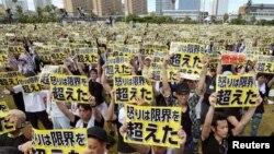 """Những người biểu tình giơ biểu ngữ với dòng chữ """"Sự tức giận đã vượt quá giới hạn"""" trong cuộc tuần hành phản đối sự hiện diện của quân đội Mỹ trên đảo Okinawa, ngày 19 tháng 6 năm 2016."""