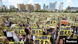 "Protesters raise placards reading ""Anger was over the limit"" during a rally against the U.S. military presence on the island and a series of crimes and other incidents involving U.S. soldiers and base workers, at a park in the prefectoral capital on Japan's southern island of Okinawa, Japan, in this photo taken by Kyodo June 19, 2016."