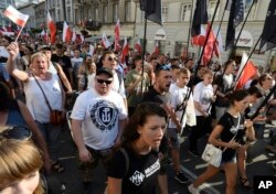 Far-right wing activists shout slogans as they march through the downtown to commemorate the 73rd anniversary of the 1944 Warsaw Uprising in Warsaw, Poland, Aug. 1, 2017.