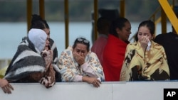 People who survived a sunken ferry, cry as they wait for more information about their missing friends and relatives, at a reservoir in Guatape, Colombia, June 25, 2017.