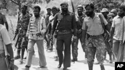 Para a história de Angola. Jonas Savimbi (no centro, com óculos escuros) f com guerrilheiros da UNITA