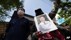 Activists gather for a rally with a photo of Thai dissident Wanchalearm Satsaksit in front of the Cambodian Embassy in Bangkok, Thailand, Monday, June 8, 2020.