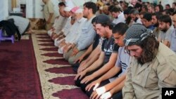 "In this photo from the Islamic State-affiliated Rased News Network, Muslim worshippers attend Friday prayers in Qaryatain, Syria, Aug. 7, 2015; a banner in the mosque read, ""Friday prayers after the conquest of Qaryatain,"" which occurred Aug. 6."