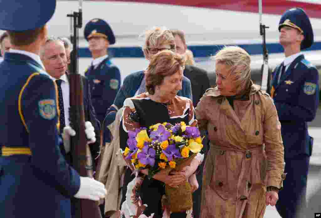European Union High Representative for Foreign Affairs and Security Policy Catherine Ashton, center, is given flowers upon her arrival in Minsk, Belarus, Aug. 26, 2014.