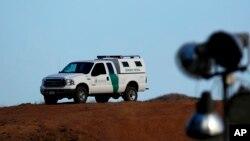 Un vehículo de la patrulla fronteriza es visto desde la frontera de Tecate, en México.