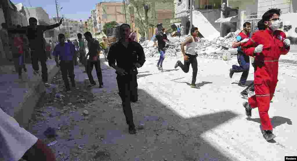 People run for cover after what activists said was shelling by forces loyal to Syria's President Bashar al-Assad in Raqqa province, eastern Syria, June 10, 2013.