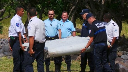Cảnh sát Pháp khiêng mảnh vỡ lớn được tìm thấy trên bãi biển ở Saint-Andre, đảo Reunion của Pháp ở Ấn Độ Dương, 29/7/2015.