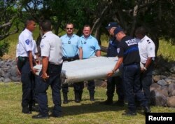 French gendarmes and police carry a large piece of plane debris which was found on the beach in Saint-Andre, on the French Indian Ocean island of La Reunion, July 29, 2015.