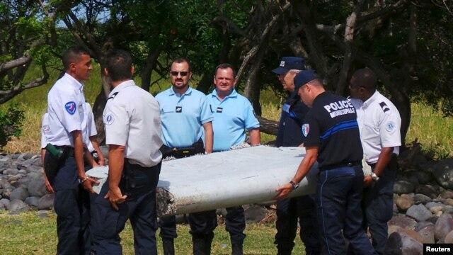 Gendarmes y policías franceses llevan una enorme pieza de un avión encontrada en la playa en Saint-Andre, la isla francesa de Reunión, en el Océano Índico.