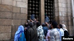 People gather as workers distribute free food for the needy from inside a mosque, during the Muslim fasting month of Ramadan in Cairo, July 10, 2013.