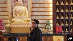 失踪马航班机中国乘客的家人在马来西亚八打灵再也的一座佛寺祈祷后讲话。(2014年3月31日 )